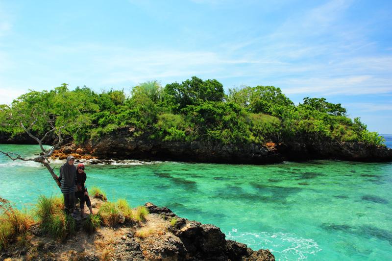 berdiri diatas batu Gili petelu dengan latar warna laut yang membiru