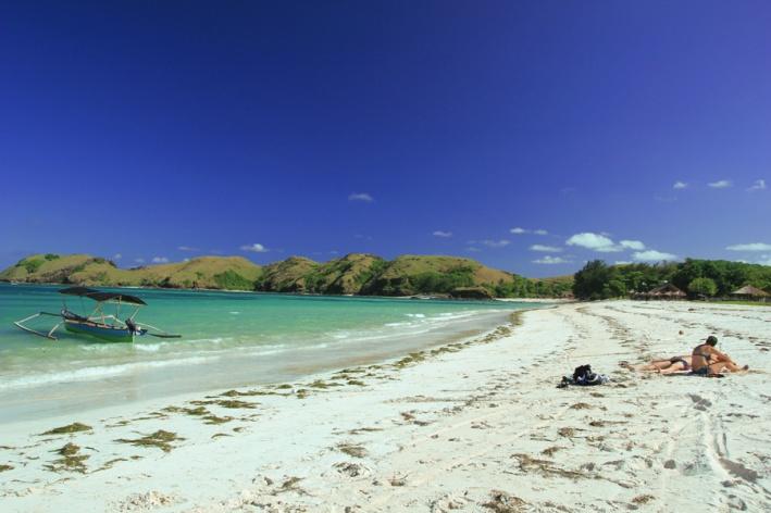 sepasang Turis sedang Sandbathing di pantai Tanjung Aan
