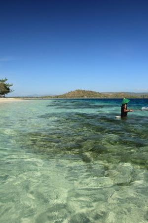 Nelayan sedang memancing diantara terumbu karang
