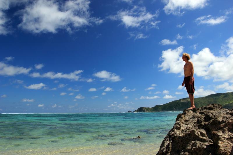 Seorang Turis yang menyukai sudut kuta yang paling sepi. Dalam keheningan dan kesepian, dia berdiri di atas batu memandangi lautan dan mendengarkan deburan ombak.