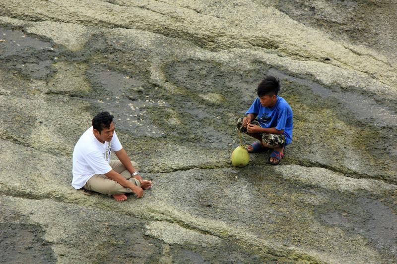 ochi menawarkan kelapa muda kepada salah satu pengunjung