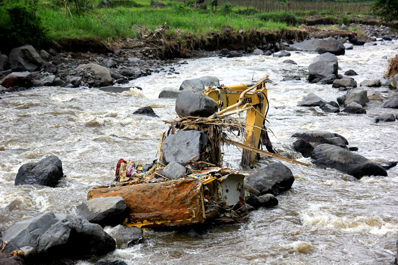 Escavator diduduki batu-batu akibat terjangan banjir bandang