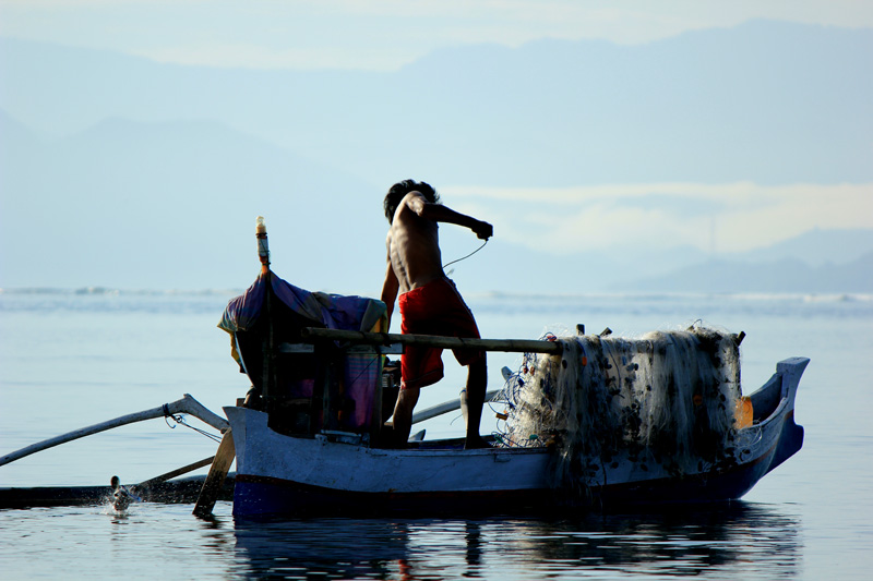 Sang Nelayan yang berusaha menghidupkan mesin perahu